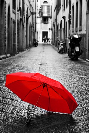 white color: Red umbrella on cobblestone street in the old town. Wind, rain, stormy weather. Color in black and white conceptual, idea. Vintage, retro style. Stock Photo