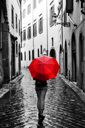Woman with red umbrella on cobblestone street in the old town. Wind, rain, stormy weather. Color in black and white conceptual, idea. Vintage, retro style. Stok Fotoğraf