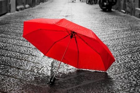 concept: Ombrello rosso su strada di ciottoli nel centro storico. Vento, pioggia, tempesta. Colore in bianco e nero concettuale, idea. Vintage, stile retrò.
