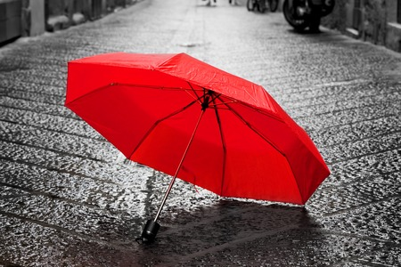 is raining: Red umbrella on cobblestone street in the old town. Wind, rain, stormy weather. Color in black and white conceptual, idea. Vintage, retro style. Stock Photo
