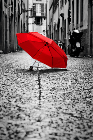 street: Red umbrella on cobblestone street in the old town. Wind, rain, stormy weather. Color in black and white conceptual, idea. Vintage, retro style. Stock Photo