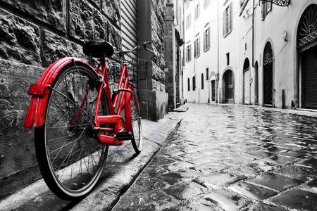 bicicleta: moto roja de la vendimia retro en la calle de adoquines, en el casco antiguo. El color en blanco y negro. Viejo concepto bicicleta encantadora.