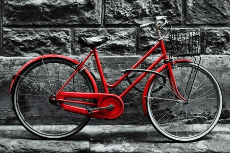 white color: Retro vintage red bike on black and white wall. Old charming bicycle concept. Stock Photo