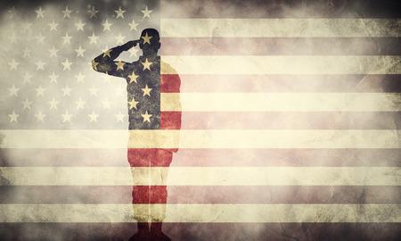 Doble exposición del soldado que saluda en la bandera del grunge EE.UU.. , Época de estilo retro. diseño patriótico Foto de archivo