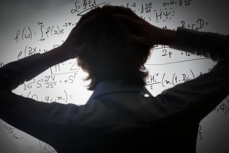 физика: Студент держась за голову, глядя на сложных математических формул на доске. Математика и концепция науки экзамен, проблему решить. Реальные уравнения, символы.