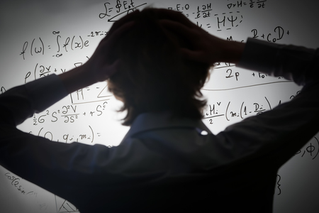 physics: Student holding his head looking at complex math formulas on whiteboard. Mathematics and science exam concept, problem to solve. Real equations, symbols.