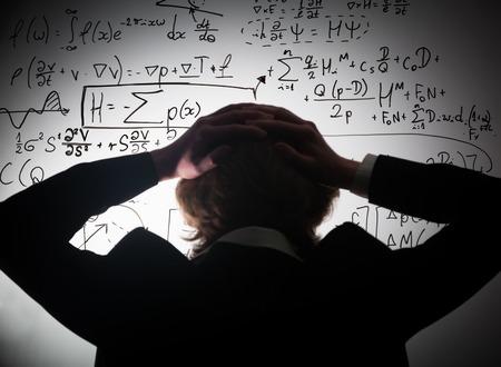 Estudiante con la cabeza mirando a fórmulas matemáticas complejas en la pizarra. Matemáticas y concepto de examen de la ciencia, problema a resolver. ecuaciones reales, símbolos. Foto de archivo