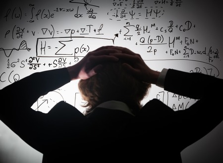 educational problem solving: Student holding his head looking at complex math formulas on whiteboard. Mathematics and science exam concept, problem to solve. Real equations, symbols.