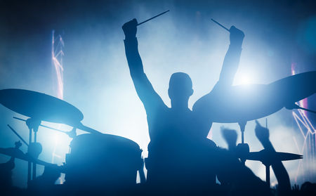 band instruments: Drummer playing on drums on music concert. Club lights, artist show. Stock Photo