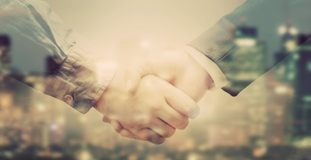 Double exposure banner of business people handshake on big city background in sunlight. Vintage colors Stock Photo
