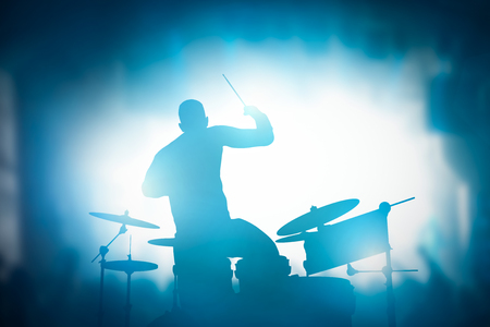 heavy: Drummer playing on drums on music concert. Club lights, artist show. Stock Photo