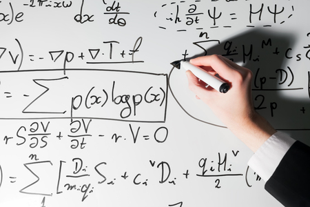 Man writing complex math formulas on whiteboard. Mathematics and science with economics concept. Real equations, symbols