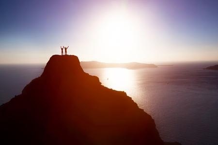 Pareja feliz en la cima de la montaña sobre el océano celebración de la vida, el éxito. Conceptos de ganar juntos, lograr el fin, la energía positiva.