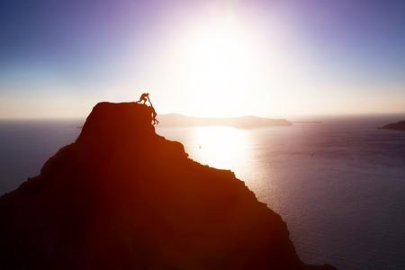 klimmer: Klimmer die hand en het helpen van zijn vriend naar de top van de berg te bereiken. Hulp, steun, hulp, teamwork in een gevaarlijke situatie concepten