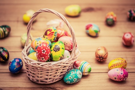 Colorful hand painted Easter eggs in basket and on wood. Traditional decoration, unique handmade design. Vintage