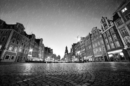 Cobblestone historic old town in rain. The market square at night. Wroclaw, Poland in black and white. Perfect empty space to put your object on the ground.