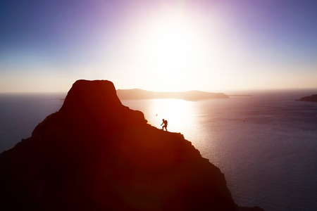 Man climbing up hill to reach the peak of the mountain over ocean. Persistence, determination, strength, reaching the target concepts. Stock Photo