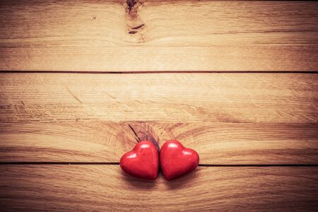 inseparable: A couple of red little hearts on wood. Vintage concept of love, Valentines Day. Copyspace for text etc.. Perfect for greeting card.