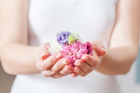 Fresh flowers in woman hand. Concept of beauty and spa, health care, aromatherapy etc.