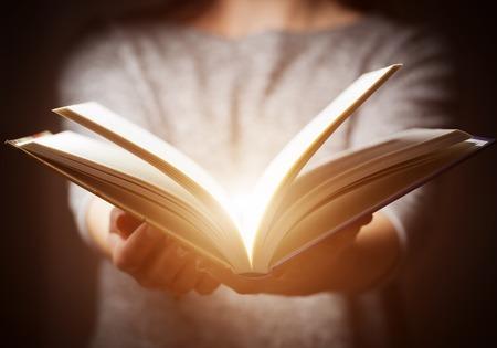Licht komt van boek in handen van de vrouw in het gebaar van het geven, aanbieden. Concept van de wijsheid, godsdienst, lezen, verbeelding.