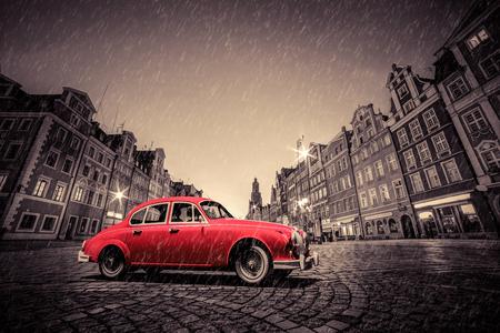 red square: Retro red car on cobblestone historic old town in rain. The market square at night. Wroclaw, Poland.