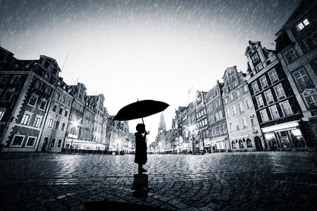 lloviendo: Niño con el paraguas de pie solo en la ciudad de adoquines en la lluvia. Concepto de perderse, solo en un mundo grande o explorar Foto de archivo