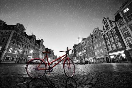 Vintage rode fiets op geplaveide historische oude stad in de regen. Kleur in zwart en wit. De markt plein in de nacht. Wroclaw, Polen. Stockfoto