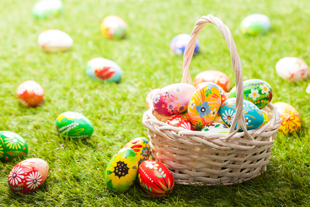 Unique hand painted Easter eggs in basket on grass. Traditional decoration in sun light