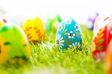 unique: Colorful hand painted Easter eggs in grass. Spring theme, white copy-space. Traditional decoration, unique handmade design. Stock Photo