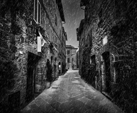 Dark narrow street in an old Italian town in Tuscany, Italy. Raining, black and white