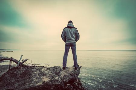 Middle-aged man standing on broken tree on wild beach looking at sea far horizon. Vintage, conceptual. Archivio Fotografico
