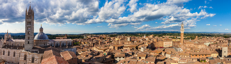 a panorama: Siena, Italy panorama rooftop city view. Siena Cathedral and Mangia Tower. Tuscany region Stock Photo