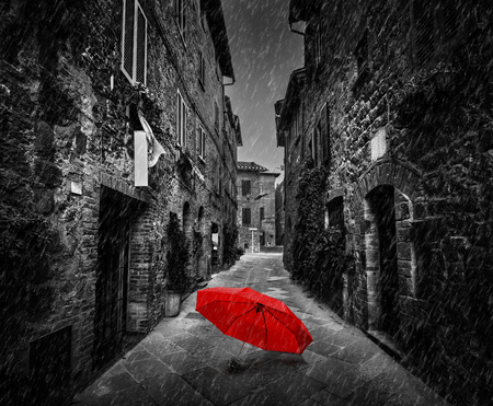 Umbrella on dark narrow street in an old Italian town in Tuscany, Italy. Raining. Black and white with red Banco de Imagens