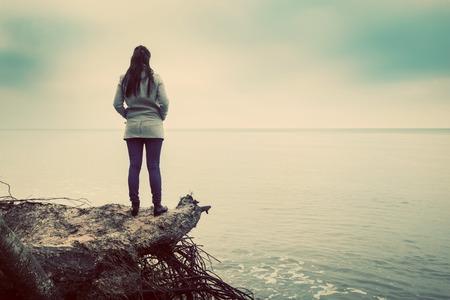 horizon: Woman standing on broken tree on wild beach looking at sea far horizon. Vintage, conceptual.
