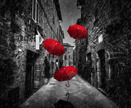 Umbrellas flying with wind and rain on dark narrow street in an old Italian town in Tuscany, Italy.. Black and white with red Foto de archivo