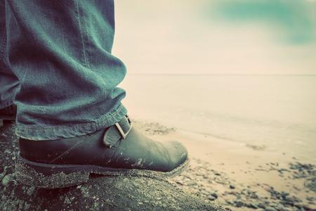 confianza: Hombre en pantalones vaqueros y zapatos elegantes de pie en el tronco de árbol caído en la playa salvaje que mira el mar. Vintage, conceptos de musculinity, la confianza, misterio, etc.