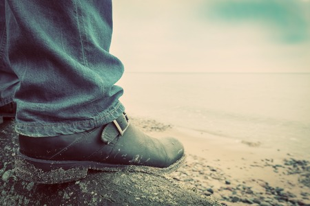 confidence: Man in jeans and elegant shoes standing on fallen tree trunk on wild beach looking at sea. Vintage, concepts of musculinity, confidence, mystery etc.