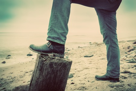 mystery man: Man in jeans and elegant shoes leaning against tree trunk on wild beach looking at sea. Vintage, concepts of musculinity, confidence, mystery etc. Stock Photo
