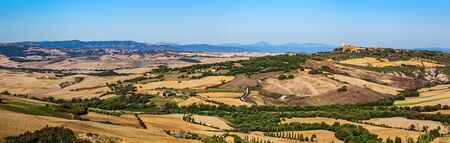 wine road: Tuscany landscape panorama with Pienza town on the hill, Italy. Cypress tree on the typical white road. Stock Photo