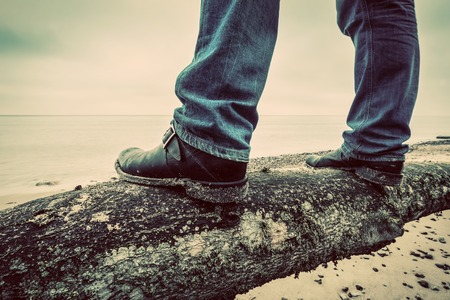 mystery man: Man in jeans and elegant shoes standing on fallen tree trunk on wild beach looking at sea. Vintage, concepts of musculinity, confidence, mystery etc.