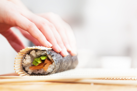Preparing, rolling sushi. Salmon, avocado, rice on seaweed and chopsticks on wooden table.