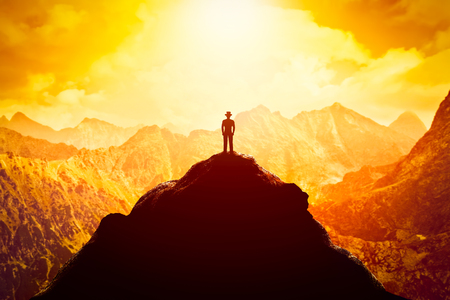 Businessman in hat on the peak of the mountain looking at sunset. Conceptual - business venture, future perspective, success, determination Stockfoto