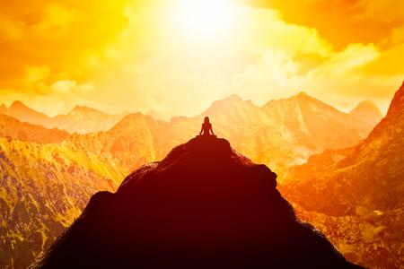 Mujer meditando en posición de yoga que se sienta en la cima de una montaña por encima de las nubes en la puesta del sol. Zen, la meditación, la paz
