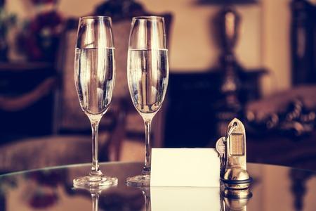 verres pleins de champagne, clés anciennes et carte blanche vierge. hôtel de luxe appartement, concept de service en chambre. Vintage, rétro.