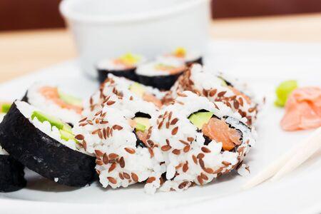 jenjibre: Sushi con salm�n, aguacate, arroz en algas y palillos servido en un plato con wasabi y jengibre. Japonesa, Comida sana asi�tica.