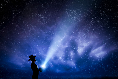 Man in hat throwing light beam up the night sky full of stars. Conceptual - explore, dream, magic, fantasy. Banco de Imagens - 54942291