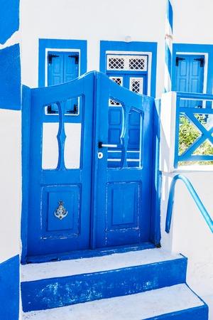 characteristic: Traditional Greek stone house, blue gate and window shutters, Santorini island, Greece. Characteristic architecture