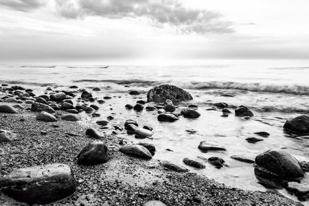 white winter: Black and white sea. Waves hitting in rocks. Wild beach Stock Photo