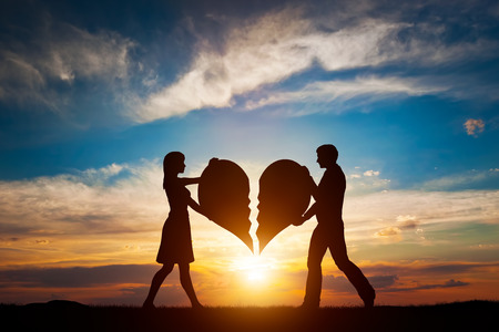 broken unity: Woman and man holding two halves of broken heart going to be joined in one. Love conceptual.