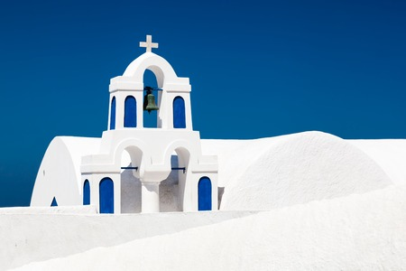 A white church with blue elements in Oia on Santorini island, Greece. Characteristic architecture and famous tourist attraction